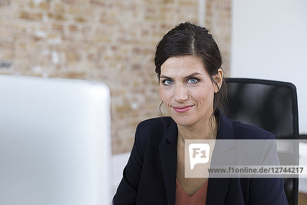 Portrait of confident businesswoman at desk in office
