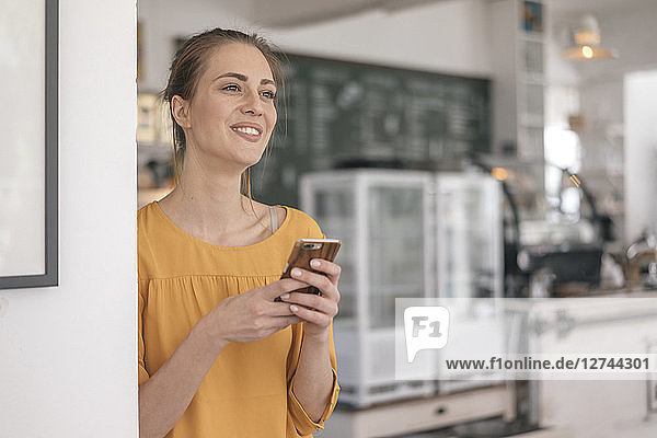 Young business owner standing in her coffee shop  using smartphone