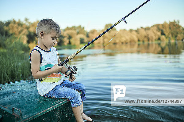 Back view of little boy with fishing rod sitting on boat