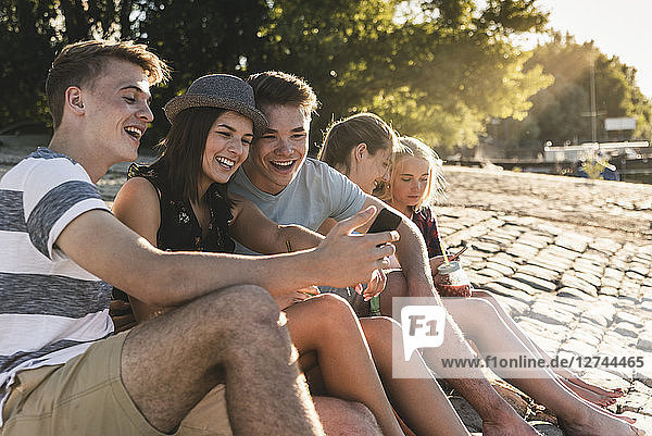 Group of friends sitting on cobblestones with refreshing drinks and cell phones