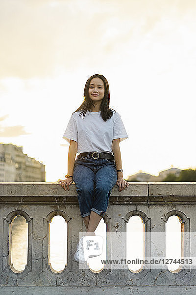 France  Paris  portrait of young woman sitting on railing at river Seine at sunset