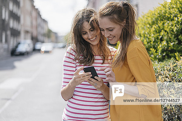 Friends in the city using smartphone  reading text messages