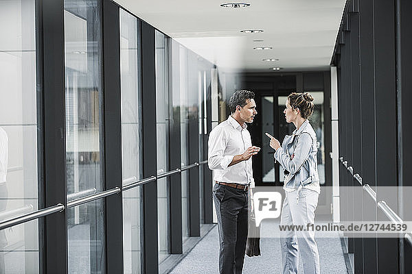Businesswoman and businessman discussing in office passageway