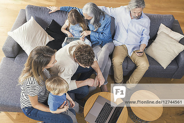 Extended family sitting on couch  using mobile devices