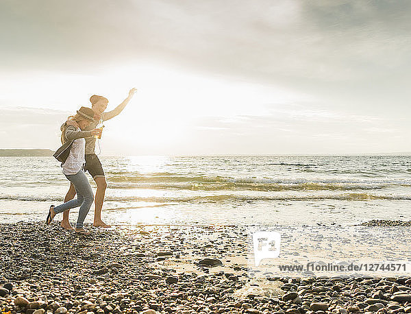Happy young couple walking on the beach at sunset