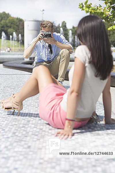 Poland,  Warsaw,  Man taking picture of young woman