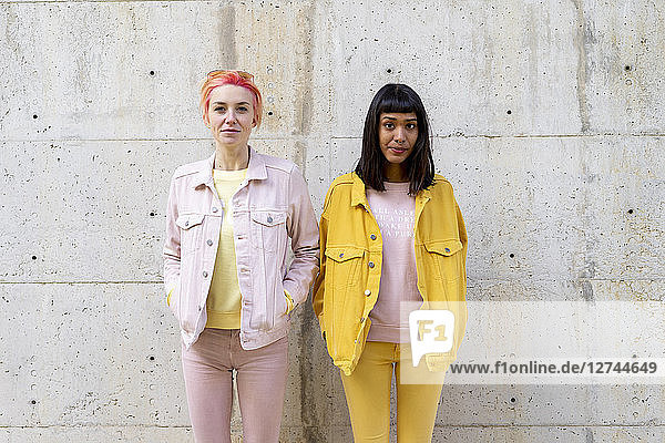 Two alternative friends having fun  wearing yellow and pink jeans clothes