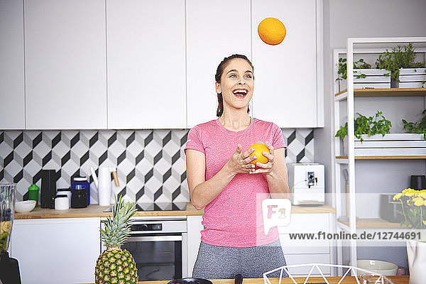 Portrait of young woman juggling with oranges in the kitchen