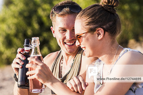 Happy young couple clinking bottles outdoors
