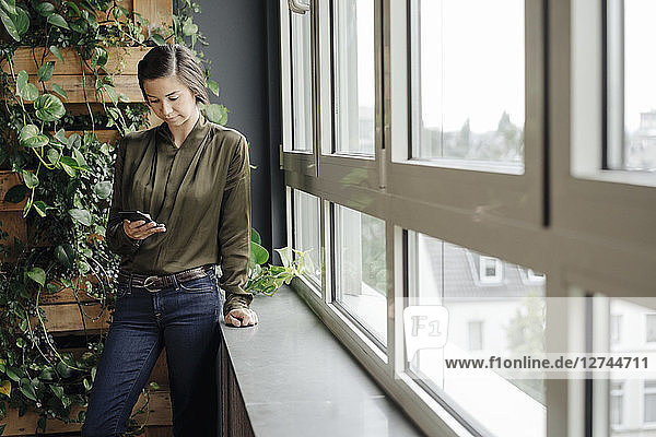 Young woman in office at the window looking at cell phone