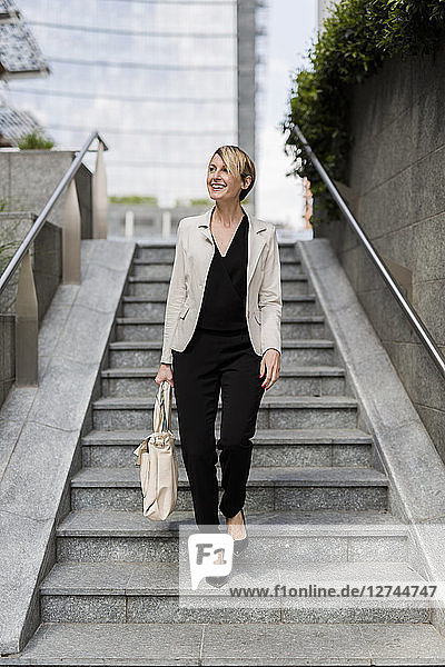 Smiling businesswoman walking downstairs