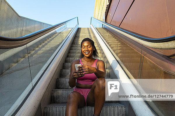 young woman sitting on escalator  using smartphone