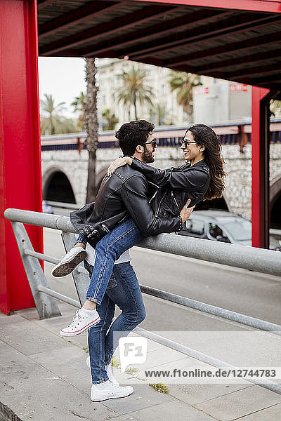 Spain  Barcelona  happy young couple embracing in the city