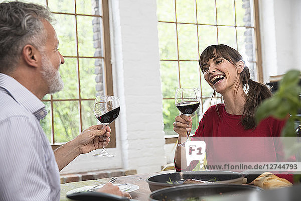 Happy couple sitting in kitchen  toasting with red wine  enjoying dinner