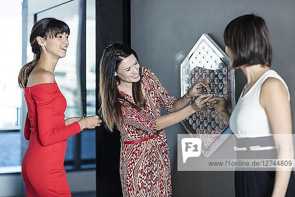 Three businesswomen doing a team building game