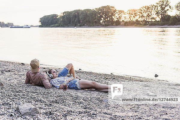 Young couple relaxing at the riverbank at sunset