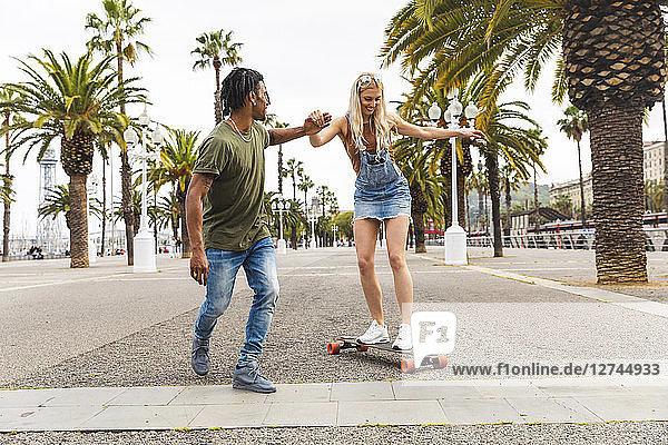 Spain  Barcelona  young man teaching his girlfriend skateboarding