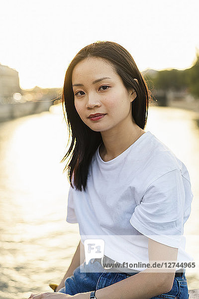 France  Paris  portrait of young woman at river Seine at sunset