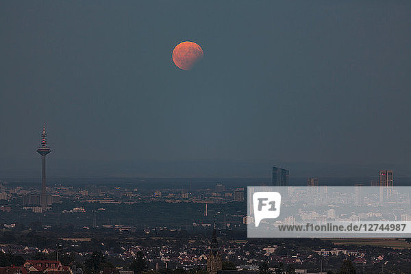 Germany  Hesse  Hochtaunuskreis  Full moon with partial eclipse rising above the city of Frankfurt