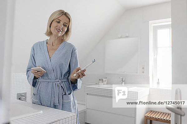 Smiling mature woman with cell phone and toothbrush in bathroom