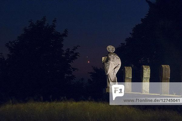 Germany  Hesse  Hochtaunuskreis  Planets Jupiter and Venus in front of a graveyard sculpture