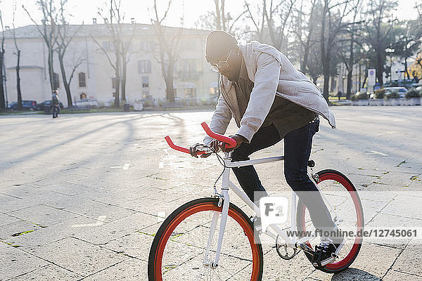 Young man riding bicycle on urban square