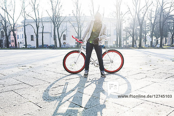Young holding bicycle on urban squre