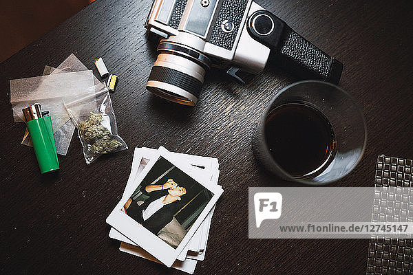 Marihuana  cigarette lighter  polaroids and analog camera on wood