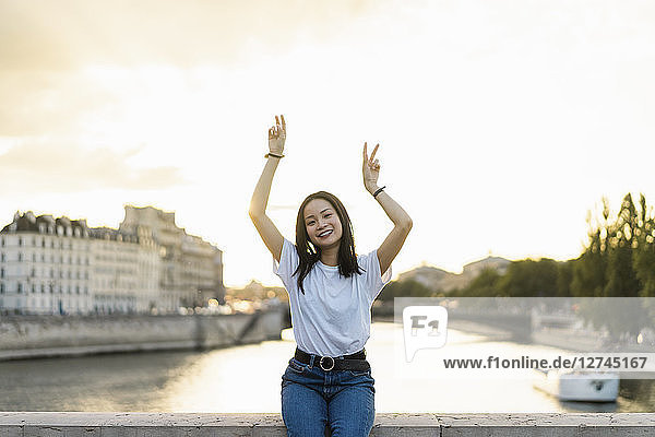 France  Paris  portrait of happy young woman at river Seine at sunset