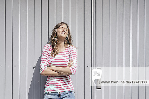 Young woman standing in front of garage doorm enjoying the sunshine
