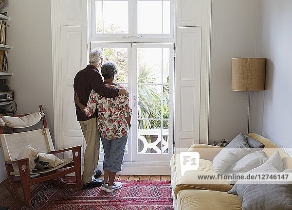 Affectionate  serene senior couple looking out living room window