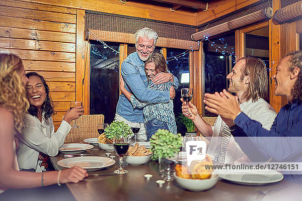Friends clapping for affectionate couple hugging at dinner table