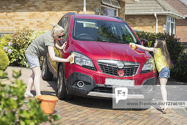 Mother and daughter washing car in sunny driveway