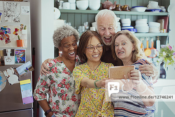 Happy  playful active seniors taking selfie with camera phone  making silly faces
