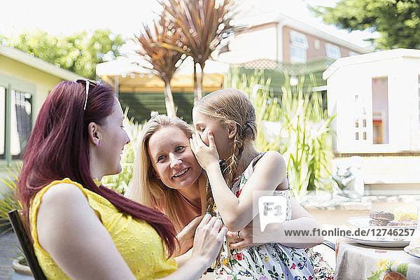 Affectionate lesbian couple holding daughter on sunny patio