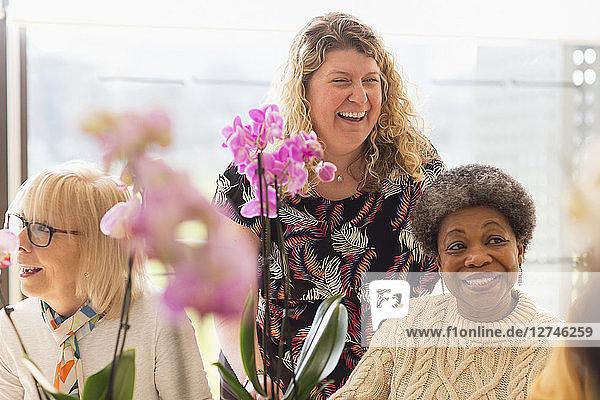 Happy instructor and active seniors enjoying flower arranging class