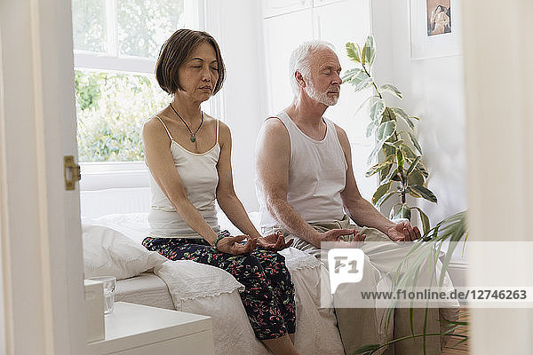 Serene senior couple meditating on bed