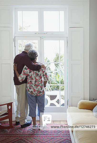Serene senior couple looking out living room window