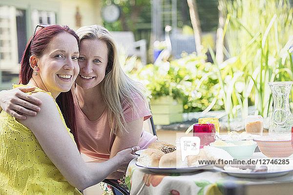 Portrait affectionate lesbian couple enjoying lunch on patio