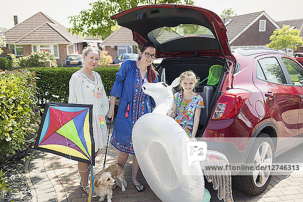 Portrait lesbian couple and daughter with kite and inflatable unicorn loading car in driveway