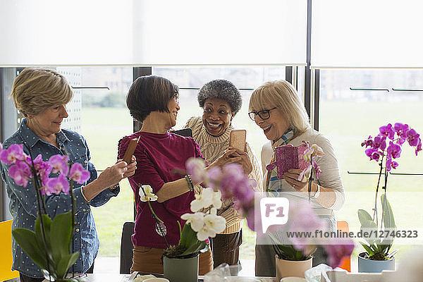 Happy senior women with camera phones enjoying flower arranging class
