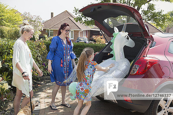 Lesbian couple and daughter loading inflatable unicorn in car hatchback