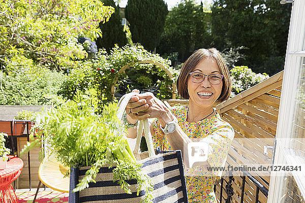 Portrait enthusiastic senior woman holding bag of fresh vegetables on balcony