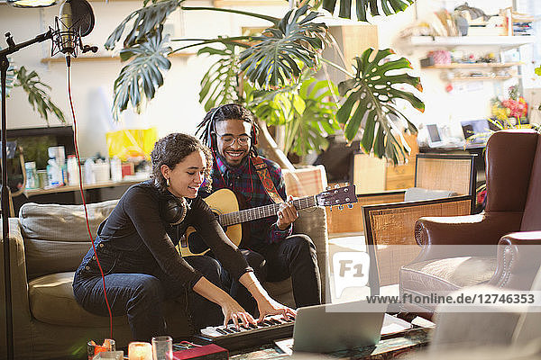 Young man and woman recording music  playing guitar and keyboard piano in apartment