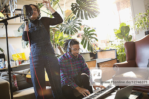 Young man and woman recording music  singing and playing piano in apartment