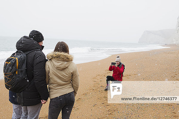 Woman with camera phone photographing husband and daughter on snowy winter beach