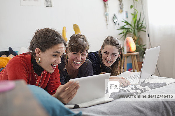 Young women friends hanging out  using digital tablet and laptop on bed
