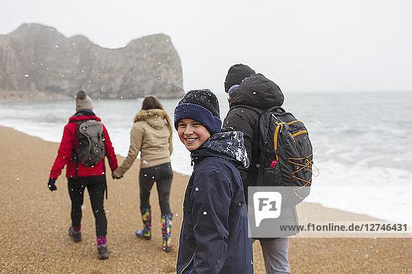 Portrait happy boy walking on snowy winter ocean beach with family
