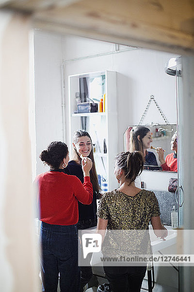 Young women friends getting ready  applying makeup in bathroom