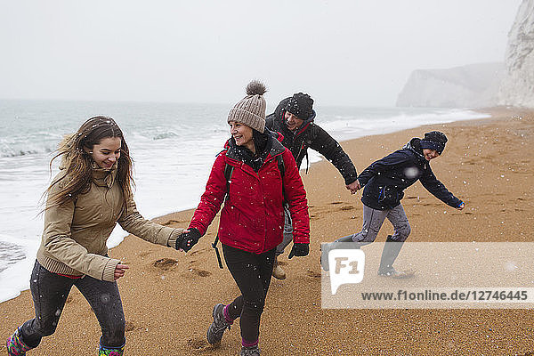 Playful family in warm clothing on snowy winter beach